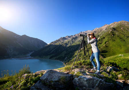 Tourist woman with hat watching trough spyglass on the lake in the mountain