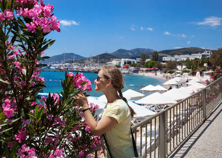 Tourist woman with pink flowers near lagoon with boats on the beach in Bodrum, Turkey
