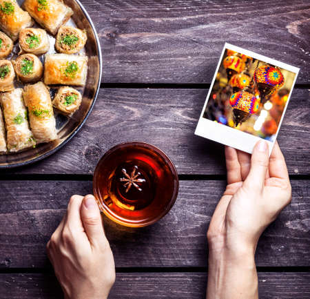 Hands with photo of oriental lantern in Istanbul grand market and black tea near Turkish baklava on wooden background
