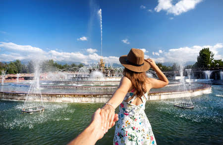 Woman in white dress and hat holding man by hand and going to fountain in the park in Almaty, Kazakhstan