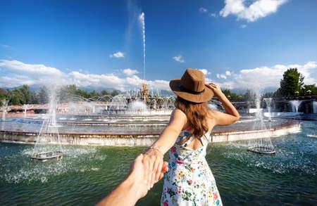 Vrouw in witte jurk en hoed bedrijf man met de hand en gaan naar fontein in het park in Almaty, Kazachstan