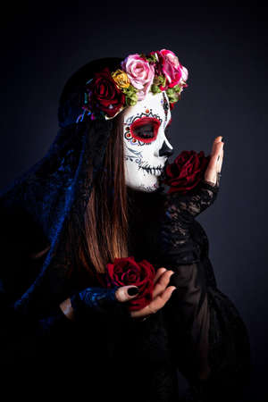 bodyart: Girl with sugar skull make up with rose flowers celebrating Day of the Dead at black background