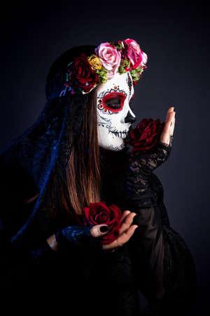 Muchacha con el cráneo del azúcar compone con flores de rosa la celebración de Día de Muertos en el fondo negro Foto de archivo
