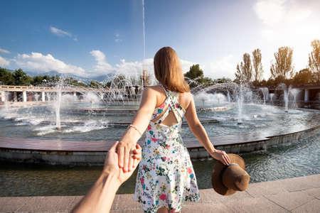Žena v bílých šatech s kloboukem drží muže za ruce a jít do kašna v parku v Almaty v Kazachstánu