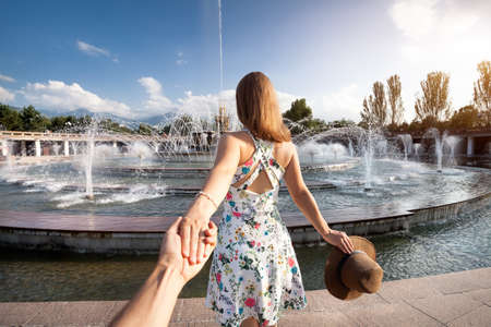 Woman in white dress with hat holding man by hand and going to fountain in the park in Almaty, Kazakhstan