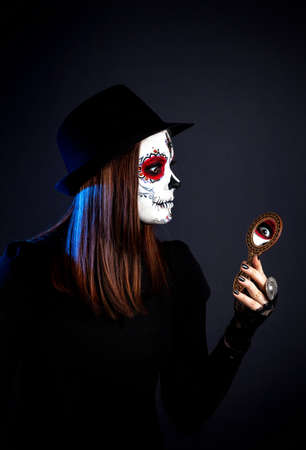 Girl with sugar skull make up looking at the mirror on the Day of the Dead at black background