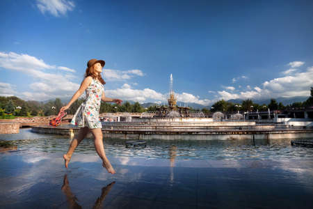 Woman in white dress and hat jump bare foot near fountain in the park in Almaty, Kazakhstan Stock Photo