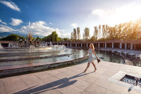 people travelling: Woman in white dress and hat going bare foot to the fountain in the park in Almaty, Kazakhstan