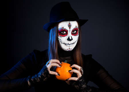 Witch with sugar skull makeup holding pumpkin at black background