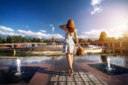 Frau im weißen Kleid und Hut mit nackten Fuß auf den Brunnen im Park in Almaty, Kasachstan