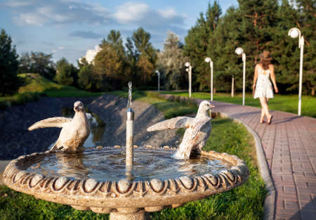 Fountain with dove statue and woman in white dress walking in the summer park in Almaty, Kazakhstan