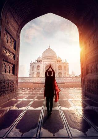 Woman doing yoga tadasana tree pose with flying red scarf in silhouette near Taj Mahal in Agra, Uttar Pradesh, India 写真素材