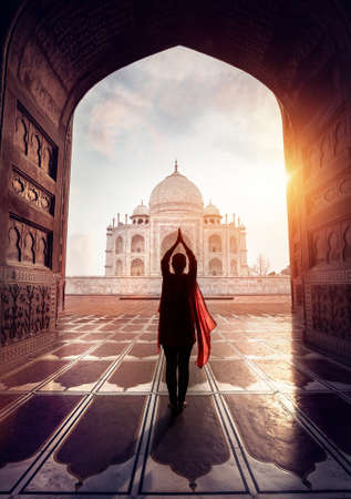 Woman doing yoga tadasana tree pose with flying red scarf in silhouette near Taj Mahal in Agra, Uttar Pradesh, India Foto de archivo