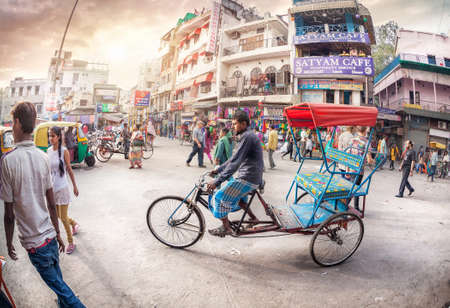 NEW DELHI, INDIA - FEBRUARY 23, 2015: Rickshaw driver at crowded street with shops, hotels, transport and people in Main Bazaar, Paharganj