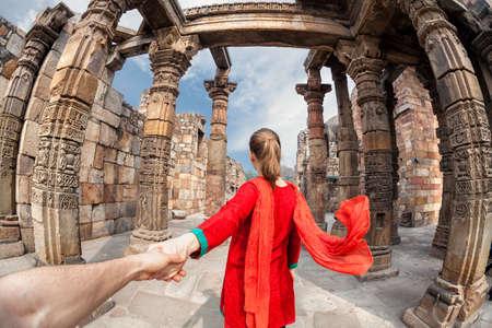 Vrouw in rood kostuum met sjaal toonaangevende man met de hand om Qutub Minar toren in Delhi, India