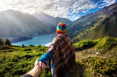 Tourist woman in rainbow hat and brown poncho holding man by hand and going to the lake in the mountains Standard-Bild