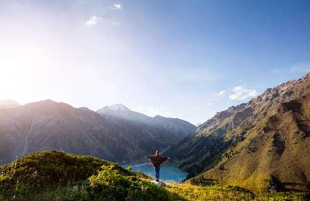 ポンチョと虹の帽子がカザフスタンの大アルマトイ湖の美しい景色を楽しみながらの観光女 写真素材 - 61298961