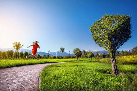 topiary: Woman in orange dress running down the road in Topiary Garden with surreal trees in cube shape Stock Photo
