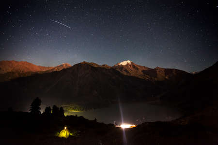 Shooting star at night sky in the mountain camp near Big Almaty Lake in Kazakhstan Zdjęcie Seryjne