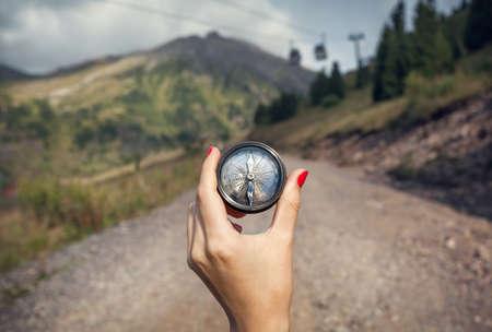Main de femme touriste avec boussole cru, sur la route de montagne