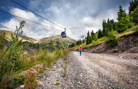ropeway: Tourist woman with backpack and yellow hat walking down the road near cableway in the mountain valley