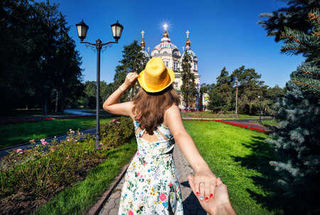 Woman in white dress and yellow hat holding man by hand and going to famous Orthodox Church in Almaty, Kazakhstan