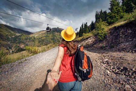 Mujer turística con mochila y sombrero amarillo que sostiene el hombre con la mano y caminando por la carretera cerca de transporte por cable en el valle de la montaña