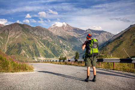 Tourist with backpack and rainbow hat walking down the road in the mountains near Big Almaty Lake in Kazakhstan photo