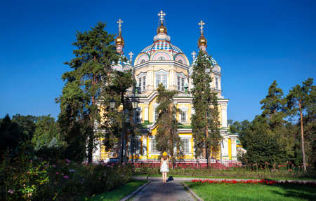 love dome: Woman in white dress and yellow hat looking to famous Orthodox Church in Almaty, Kazakhstan Stock Photo