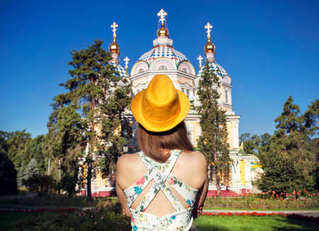 Woman in white dress and yellow hat looking to famous Orthodox Church in Almaty, Kazakhstan Stock Photo
