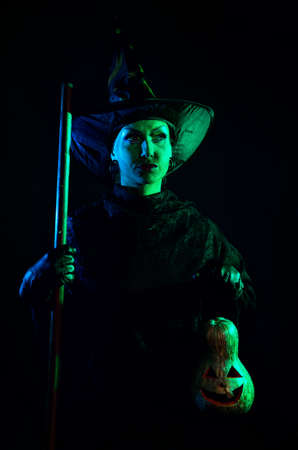 Witch with green skin holding carved Halloween pumpkin lantern at dark background