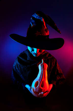 Witch holding carved Halloween pumpkin lantern at dark background with blue and pink lights Stock Photo