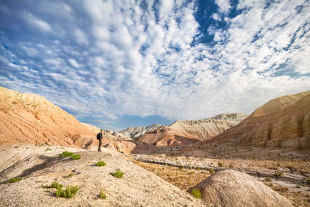 Tourist man with backpack in Altyn Emel National Desert Park with Aktau Mountains at beautiful sunrise in Kazakhstan photo