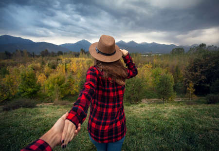 discover: Woman in red checked shirt and hat holding man by hand going to Autumn forest with mountains and cloudy sky