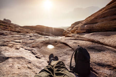 Tourist with backpack at Extinct volcano Bektau Ata in the desert of eastern Kazakhstan Stock Photo