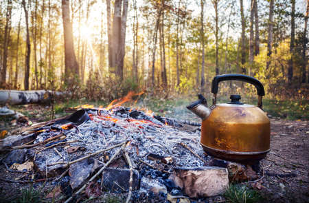 Smoky tourist kettle on fire in morning forest at sunrise