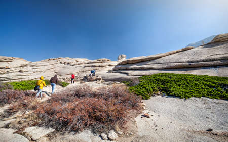 ata: People in colorful jackets walking through the rocky desert at hot day in Kazakhstan Stock Photo