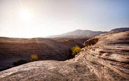 Layered volcanic canyon in the desert with mountains at beautiful sunset