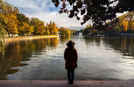 siluet: Woman with hat in silhouette near the lake with yellow autumn trees in the park