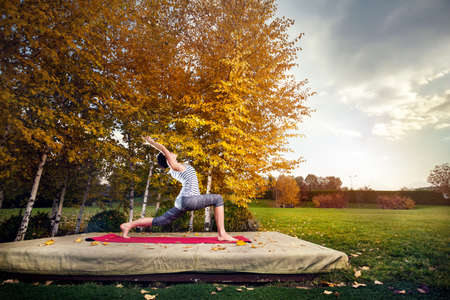 yellow trees: Young woman doing yoga in autumn city park near yellow birch trees Stock Photo