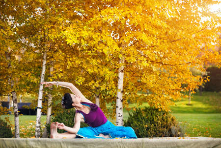Young woman doing yoga in autumn city park near yellow birch trees Stock Photo