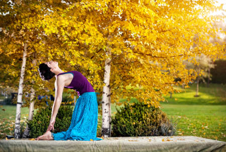 ushtrasana: Young woman doing yoga in autumn city park near yellow birch trees Stock Photo