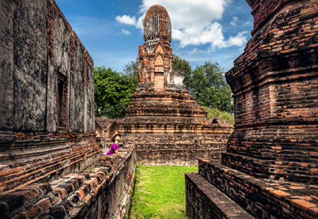 Woman in hat looking at ancient ruined city in Lopburi, Thailand