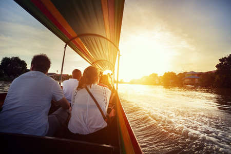 discovery channel: Tourist sitting in long-tail boat cruise by Chao Phraya river in Ancient city Ayutthaya at Sunset, Thailand