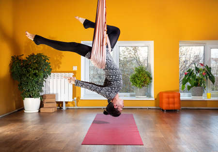 yellow walls: Young woman doing antigravity yoga at wellness studio with yellow walls Stock Photo