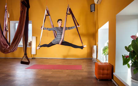 yellow walls: Young woman doing antigravity yoga leg split position at wellness studio with yellow walls