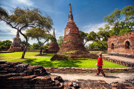 Tourist Woman in red costume looking at ancient ruined stupas in Ayutthaya Historical park, Thailand Stock Photo