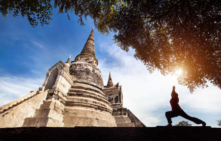 Woman doing Yoga warrior pose near historical temple in silhouette in Ayutthaya Historical Park, Thailand Stock Photo