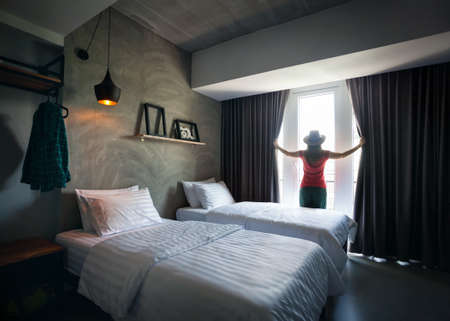 Woman in the beautiful and bright hotel room opening the curtains. Travel concept. Banco de Imagens