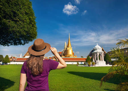 Tourist woman in hat looking at big golden Stupa in Wat Phra Kaew in Bangkok, Thailand